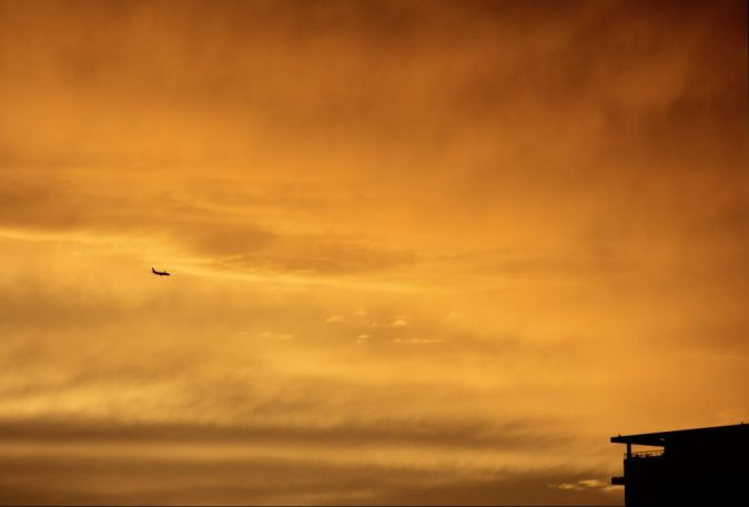 airplane flying over chicago at sundown